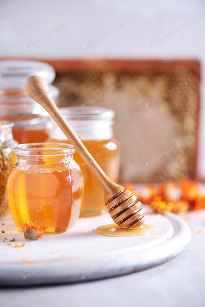 Herbal honey in jar with dipper, honeycomb