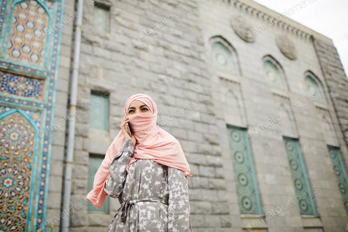 Muslim woman communicating on phone