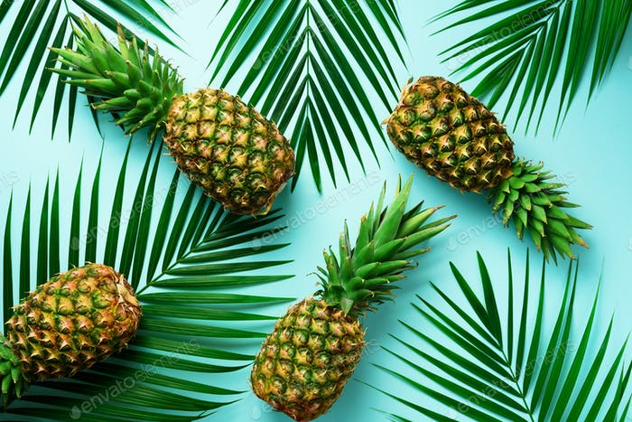 Pineapples and tropical palm leaves on pastel turquoise background. Summer concept. Creative flat