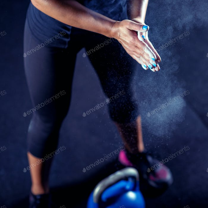 Woman athlete putting weightlifting chalk