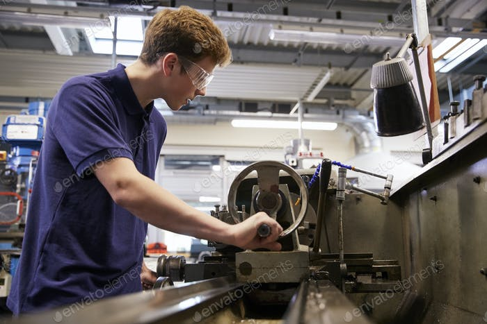 Male Teenage Apprentice In Engineering Factory Using Lathe