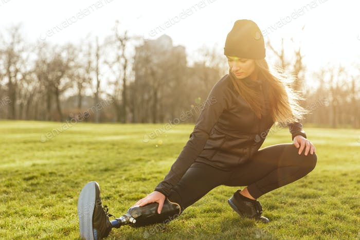 Photo of concentrated disabled girl in sportswear, doing sport e