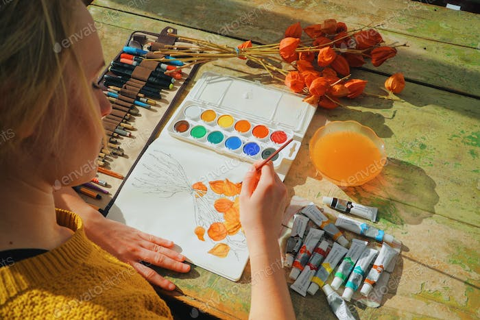 Female artist painting a picture of a flower with brush and watercolors - art is property released