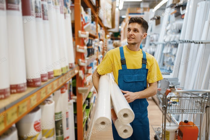Builder with roll of wallpapers in hardware store