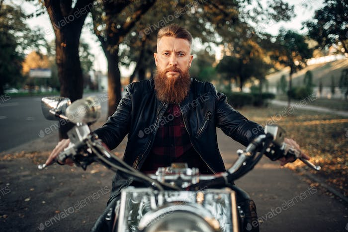 Bearded motorcyclist sitting on classical chopper