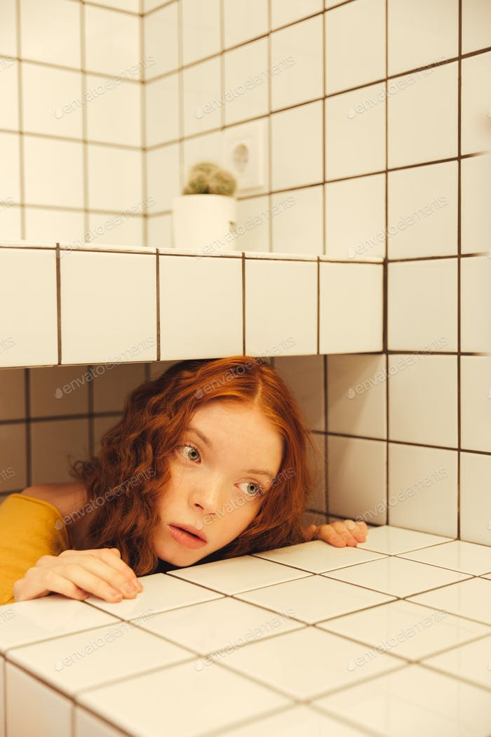 Concentrated young redhead curly woman sitting in cafe