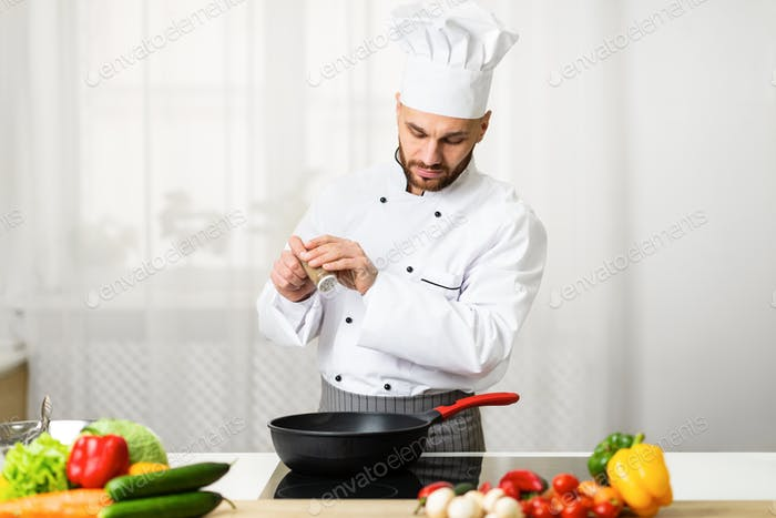 Chef Adding Pepper In Frying Pan Seasoning Dish In Kitchen