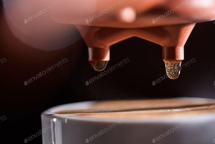 Makro-Foto einer Tasse heißen Kaffee aus der Kaffeemaschine. Professionelles Kaffeebrauen