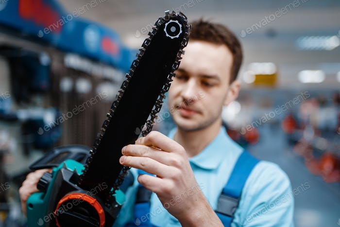 Worker in uniform holds electric saw in tool store