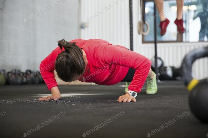 Fit Female Athlete Doing Pushups In Health Club