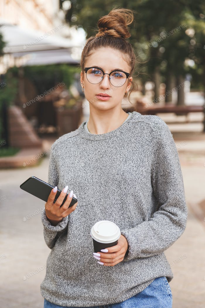 Young girl dressed in casual clothes with smartphone and a cup of takeaway coffee