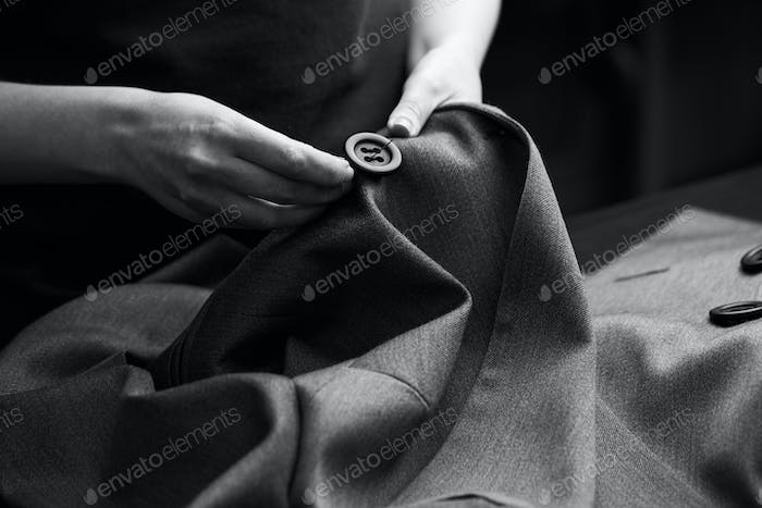 Sewing the buttons to the jacket
