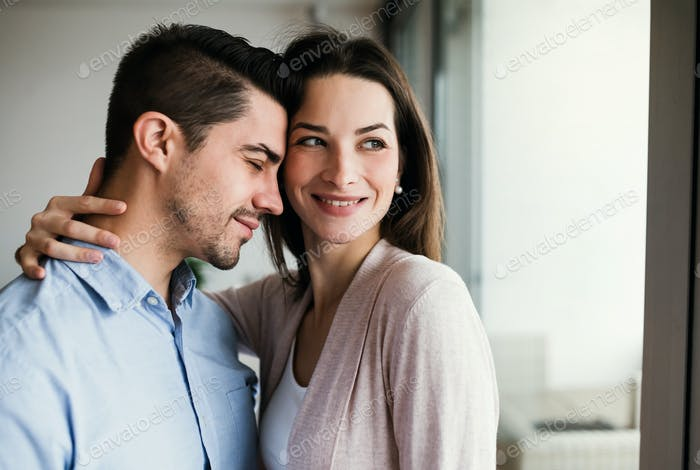 Young couple in love standing by the window at home, hugging. Copy space.