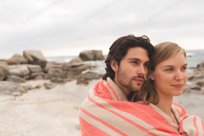 Caucasian couple wrapped in blanket standing at beach on a sunny day.