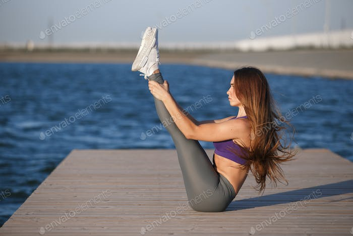 Young girl with long brown hair dressed in a sports top and tights is doing stretching on the wooden