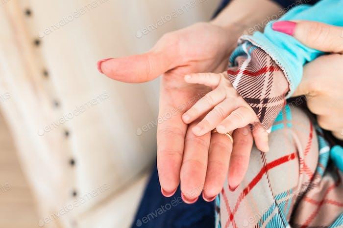 Konzept der Liebe und Familie. Hände von Mutter und Baby Nahaufnahme