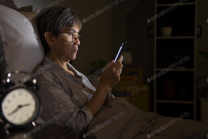 Senior woman using smartphone at night