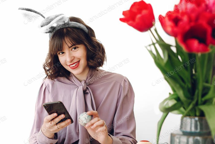Beautiful stylish girl in bunny ears smiling and painting easter eggs on rustic table