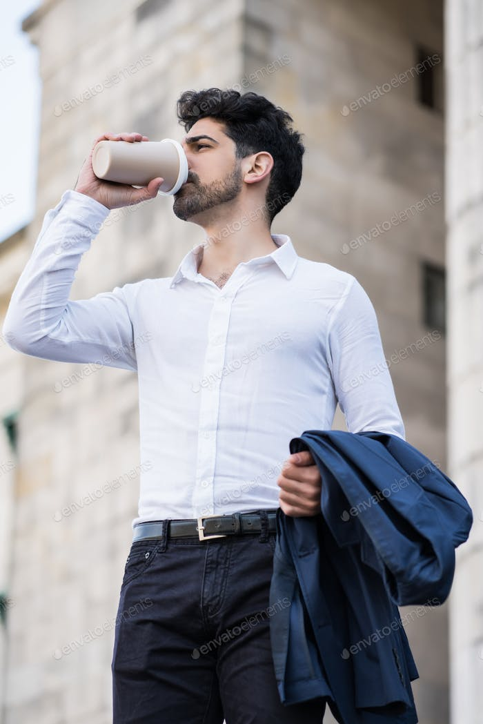 Businessman drinking a cup of coffee on way to work.