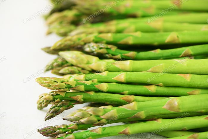 Grüner frischer Spargel auf grauem Hintergrund. Draufsicht. Rohes, veganes, vegetarisches und sauberes Esskonzept