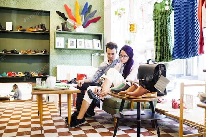 Mann Blick auf Frau versuchen Schuh im Laden