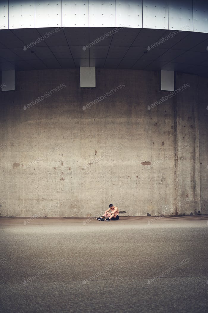 Distance shot man sitting against concrete wall