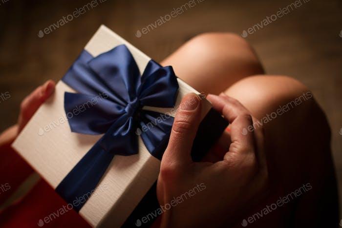 Frau öffnet eine Pappe Geschenkbox mit blauem Band