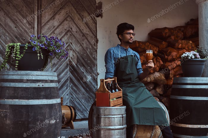 Brewmaster sitting on a wooden barrel and holds a glass of craft beer, relaxes after work.
