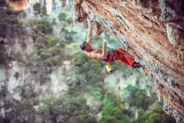 Kletterer schneiden Seil beim Klettern herausfordernde Route auf Klippe