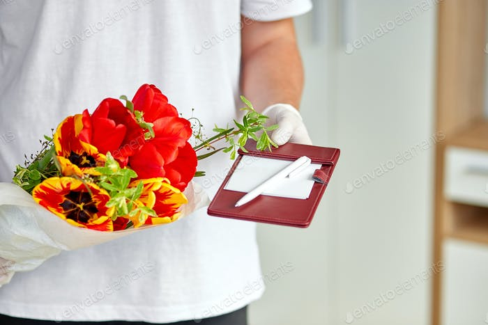 Courier, delivery man in medical latex gloves safely delivers online purchases a bouquet of flower