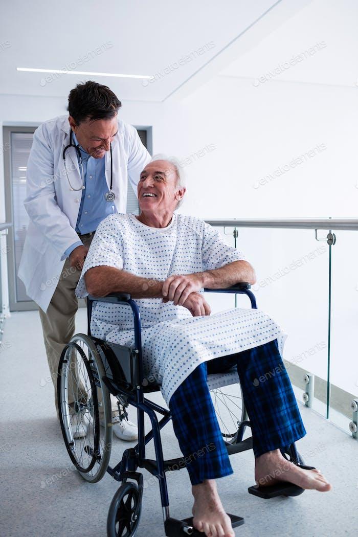 Arzt interagiert mit männlichen älteren Patienten auf einem Rollstuhl