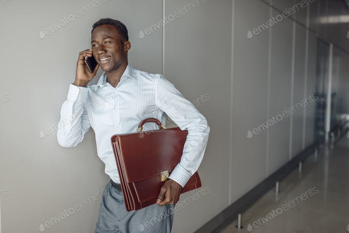 Businessman talking by phone in office hallway
