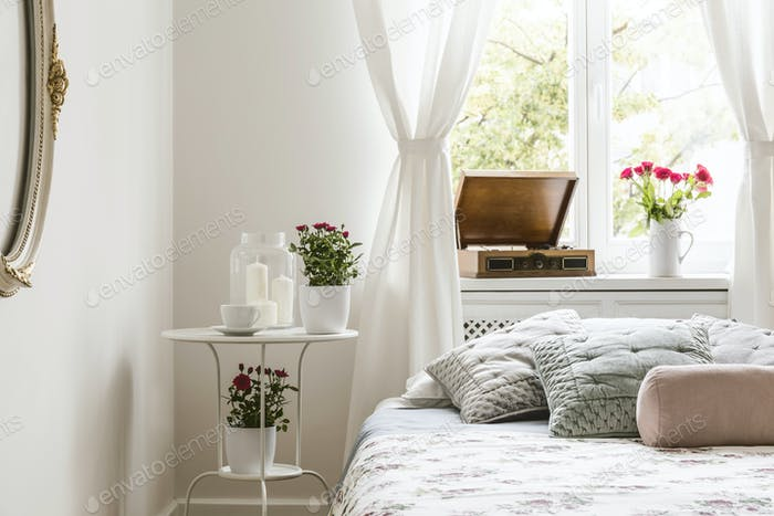 White bedroom interior in real photo with bedside table with tea
