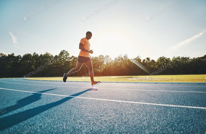 Fit young athlete running along a track in the afteroon