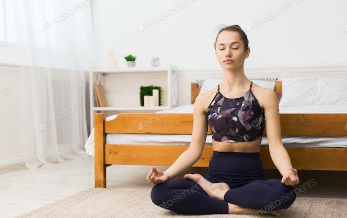 Junge Frau Ausübung in Lotusposition im Schlafzimmer