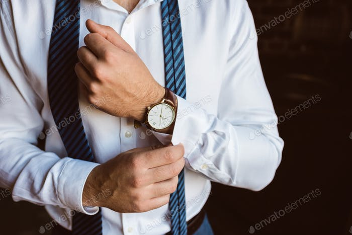 cropped shot of businessman fixing cufflink