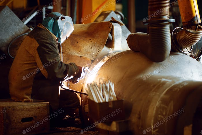 Welder in mask works with metal construction