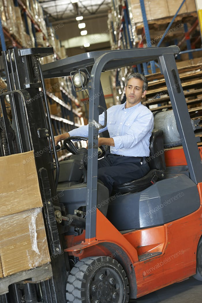 Man Driving Fork Lift Truck In Warehouse