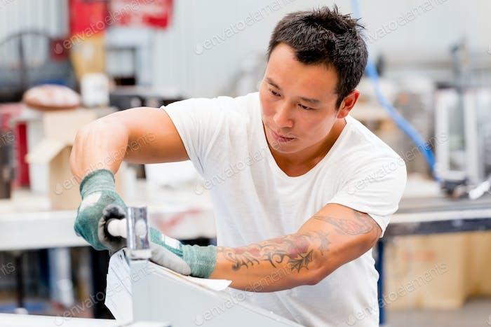 Asiatische Arbeiter in Produktionsanlage auf der Fabrikhalle
