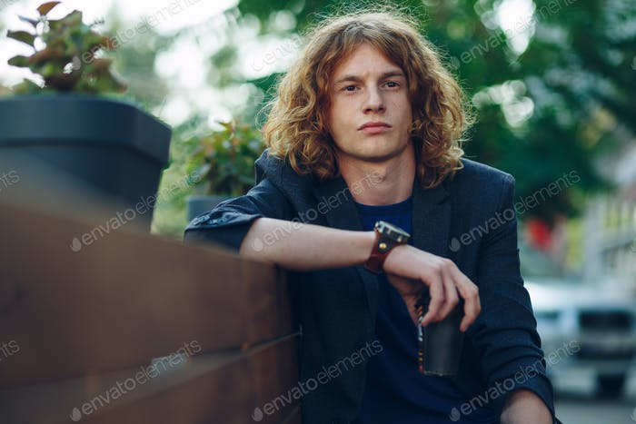 Red haired hipster man sitting on bench with coffe to go