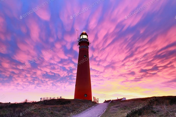 spectacular purple mammatus clouds over red lighthouse