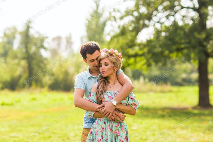 happy young couple hugging on nature