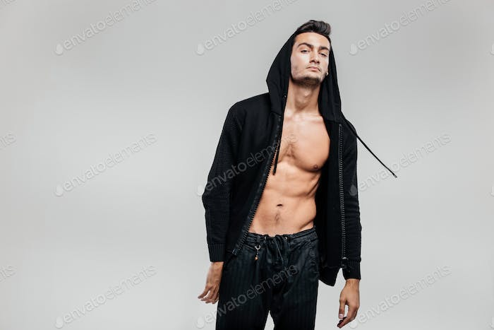 Stylish young dancer of street dancing dressed in a sweatshirt on a naked torso with a hood and