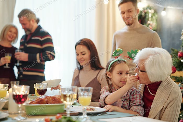 Adorable girl giving her great grandmother small tomato by festive table