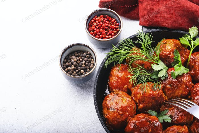 Meatballs with tomato sauce and spices in frying pan