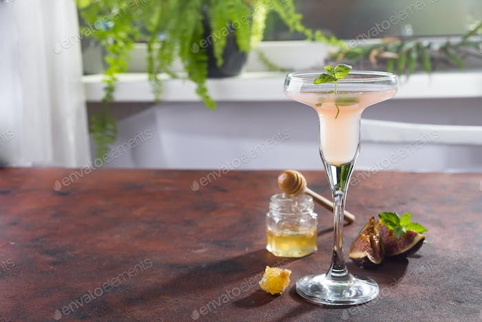 Bellini cocktail with peach and figs, honey on brown background over window
