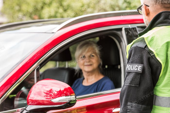 Policeman talks to an elderly lady sitting in a luxurious red car
