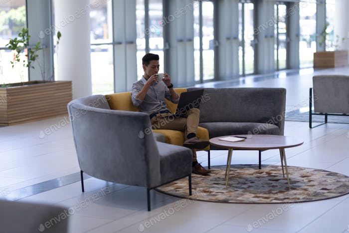 Male executive having coffee while using laptop sitting in the lobby at office