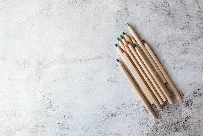Wooden colored pencils on the gray background