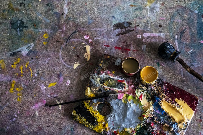 High angle close up of painter's palette and paintbrush in a workshop.